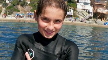 A photo of Brayden in a wetsuit, posing in front of an ocean