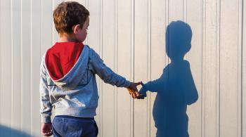 A photo of a child with his back to the camera, touching his shadow reflection