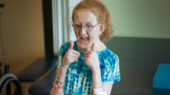 A photo of Ellie, a Kennedy Krieger patient, giving two thumbs up to the camera