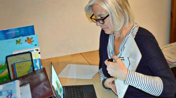 A therapist looks at a laptop screen as she carries out a telehealth appointment