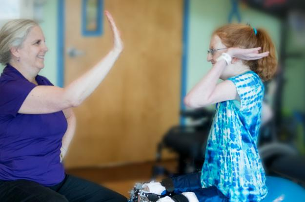 Kennedy Krieger patient Ellie high-fives a therapist